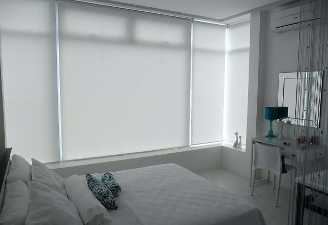 White Roller Blinds Installed in a Relaxing White Bedroom